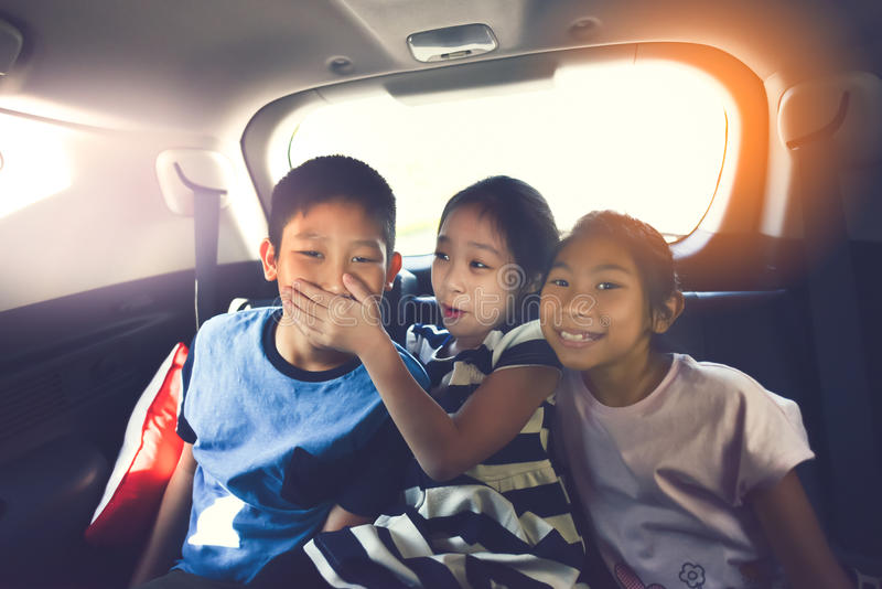 Happy Asian kids travelling in car. stock photo