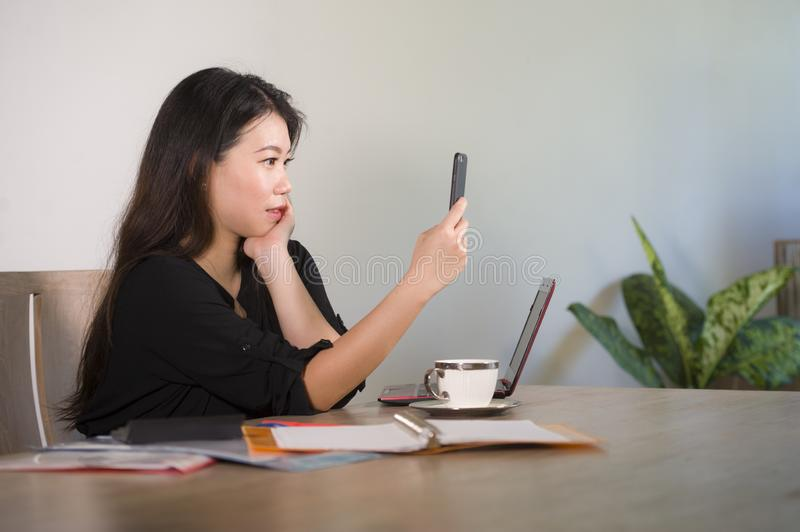 Happy Asian Korean businesswoman taking selfie photo with mobile phone at corporate company office desk smiling playful in female stock photo