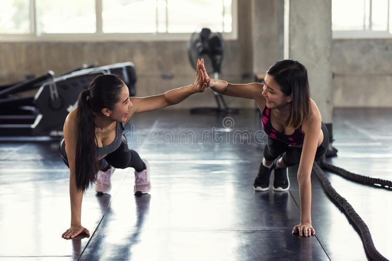 Happy Asian LGBT friends sit up in gym stock photos