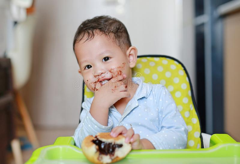 Happy Asian little baby boy sitting on children chair indoor eating bread with Stuffed Chocolate-filled dessert and Stained around. Her mouth stock images