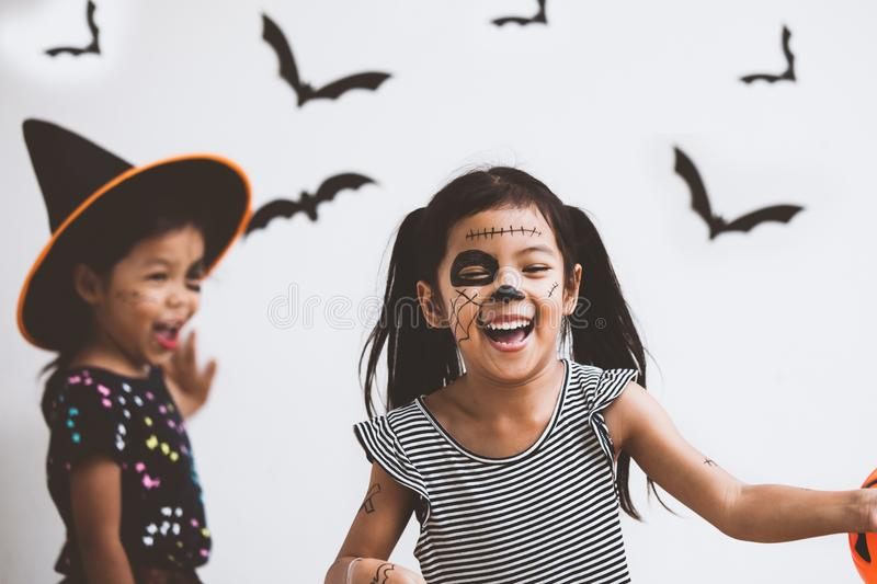 Happy asian little child girl having fun on Halloween celebration. Happy asian little child girl in costumes and makeup having fun on Halloween celebration royalty free stock images