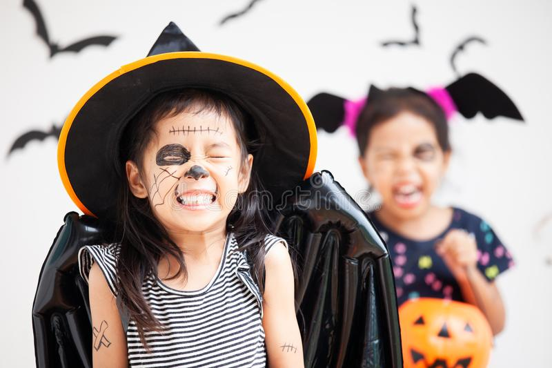 Happy asian little child girl having fun on Halloween celebration. Happy asian little child girl in costumes and makeup having fun on Halloween celebration royalty free stock photo