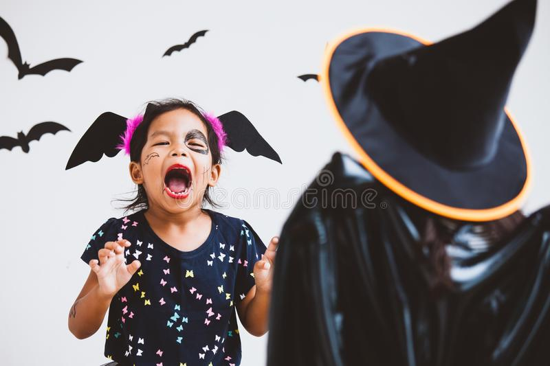 Happy asian little child girl having fun on Halloween celebration. Happy asian little child girl in costumes and makeup having fun on Halloween celebration royalty free stock photography
