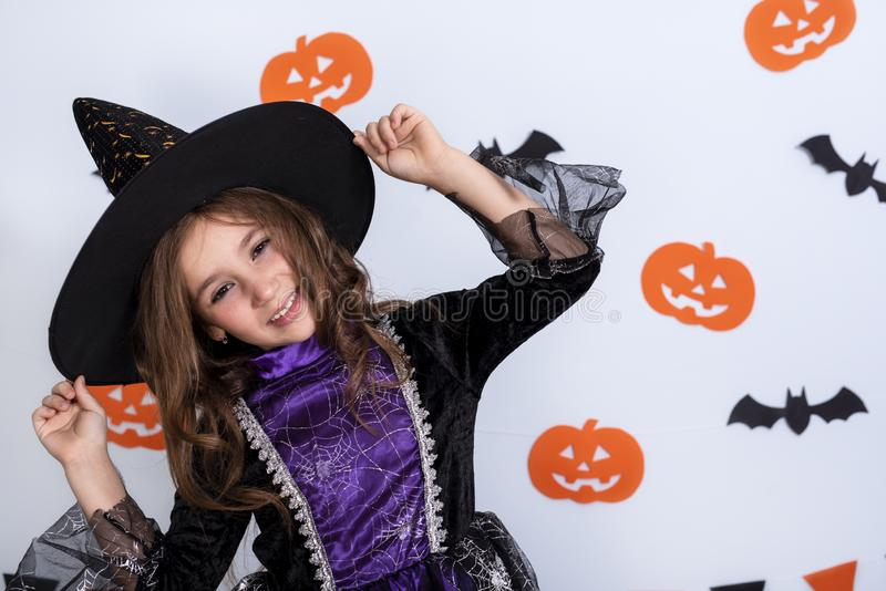 Happy little girl in costumes and makeup having fun on Halloween celebration over white background with bats and pumpkin. Happy asian little child girl in royalty free stock image