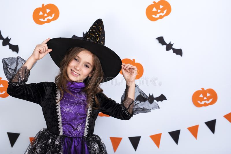 Happy little girl in costumes and makeup having fun on Halloween celebration over white background with bats and pumpkin. Happy asian little child girl in royalty free stock photos