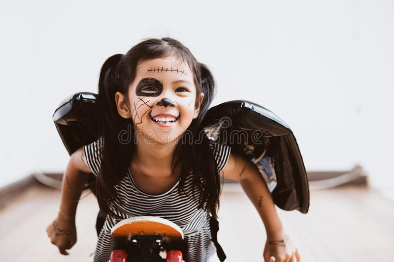 Happy asian little child girl having fun on Halloween celebration. Happy asian little child girl in costumes and makeup having fun to play with roller board, She stock photos