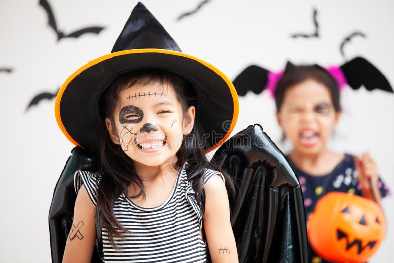 Happy asian little child girl having fun on Halloween celebration. Happy asian little child girl in costumes and makeup having fun on Halloween celebration stock photography