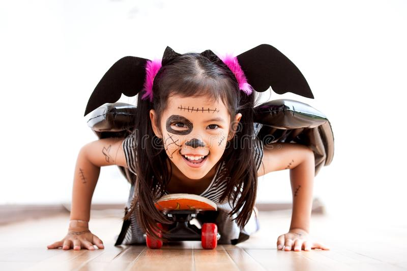 Happy asian little child girl having fun on Halloween celebration. Happy asian little child girl in costumes and makeup having fun to play with roller board, She royalty free stock image