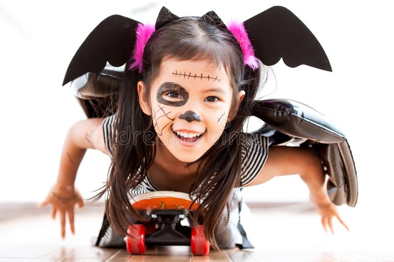 Happy asian little child girl having fun on Halloween celebration. Happy asian little child girl in costumes and makeup having fun to play with roller board, She stock image