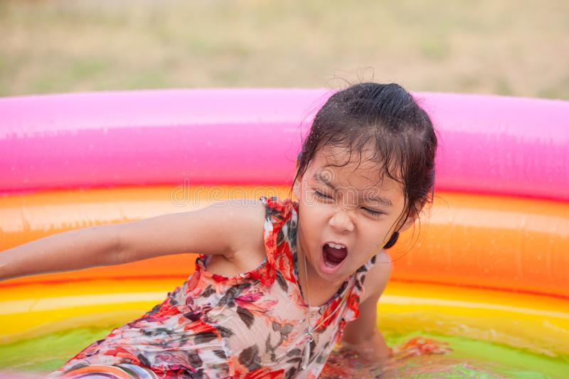 Happy asian little child girl having fun to play water stock image
