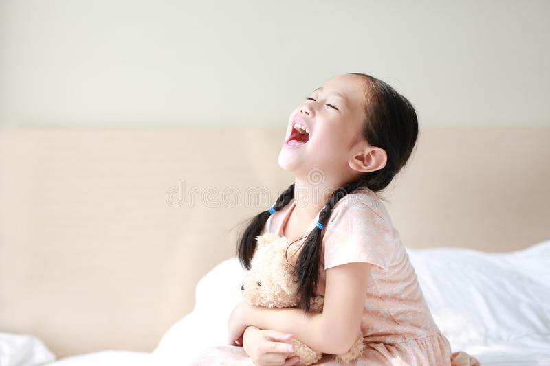 Happy Asian little child girl hugging teddy bear while sitting on the bed at home stock photos