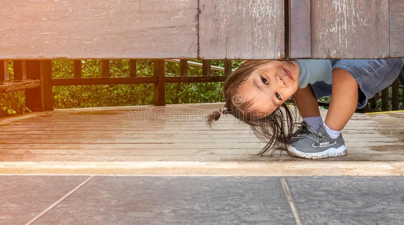 Happy Asian little child girl plays peekaboo under the wooden door in the garden royalty free stock images
