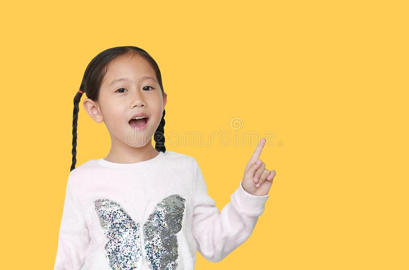 Happy Asian little child girl pointing forefinger up isolated over yellow background with copy space. Cheerful emotion concept stock photo