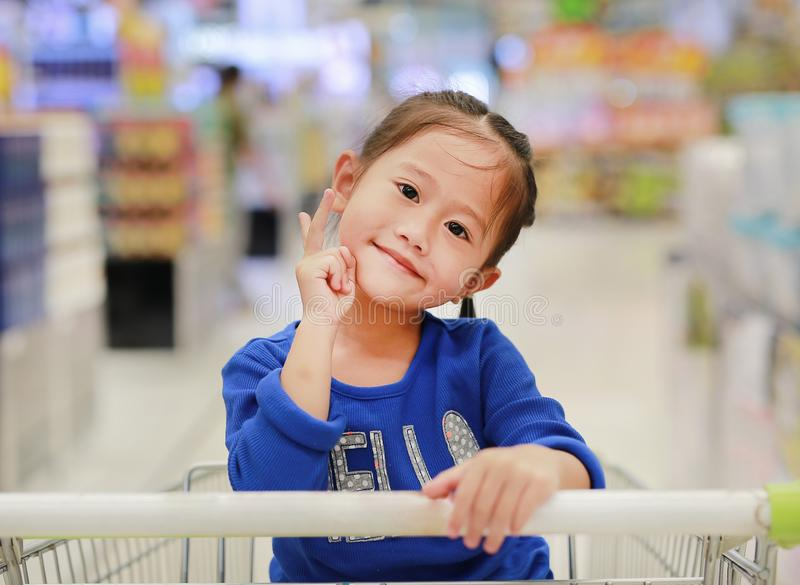 Happy Asian little child girl sitting in the trolley during family shopping in the market stock photo