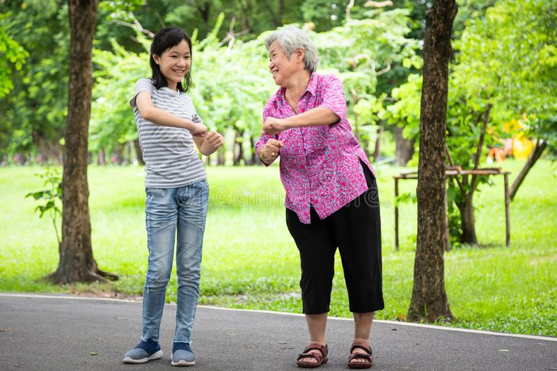 Happy asian little child girl smiling and exercise with elderly woman in outdoor park,granddaughter,senior grandmother dancing, royalty free stock photo
