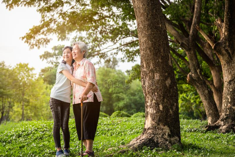 Happy asian little child girl support,hugging senior grandmother,smiling granddaughter in outdoor park,elderly woman with walking royalty free stock photo