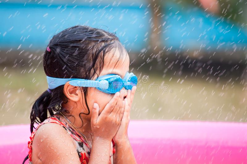 Happy asian little child girl wearing swimming goggles. Having fun to play water in the pool in summer time stock photography