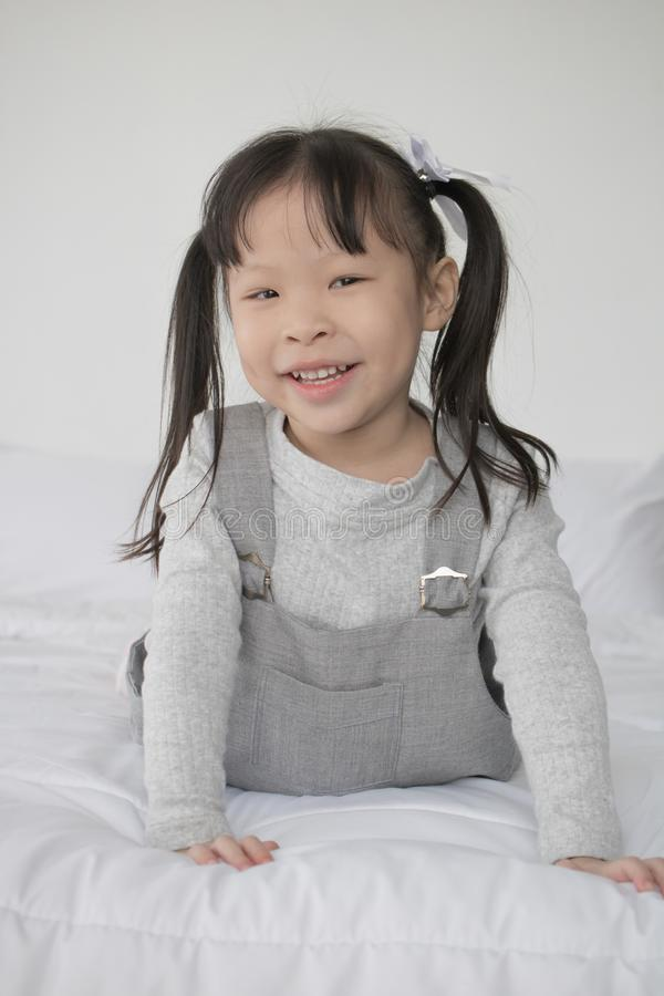 Happy Asian little cute girl lying on bed and smile stock image