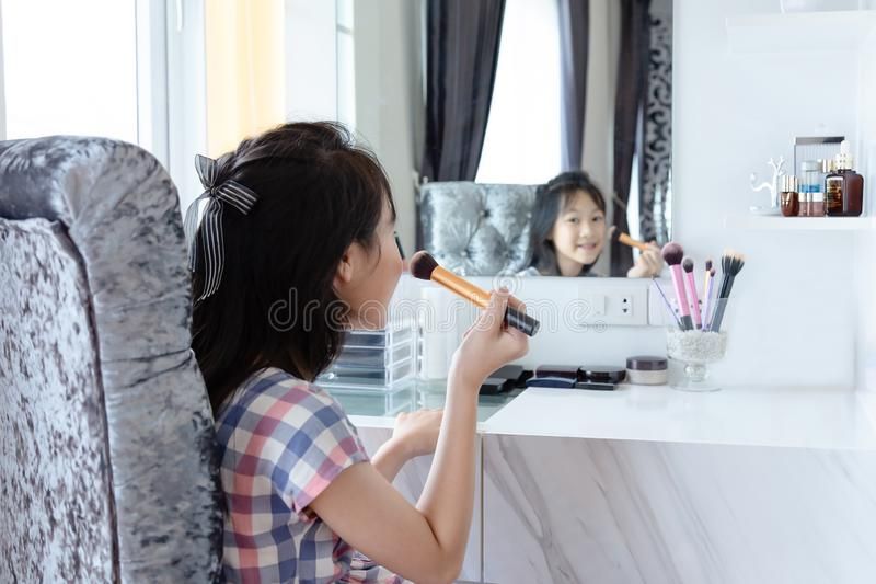 Happy asian little girl, adding some color to my cheeks and applying foundation powder or blush with makeup brush,side view of ch stock photo