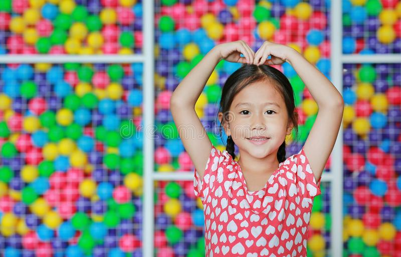 Happy Asian little girl doing heart sign on head against colorful ball playground. Expresses love emotions.  stock images
