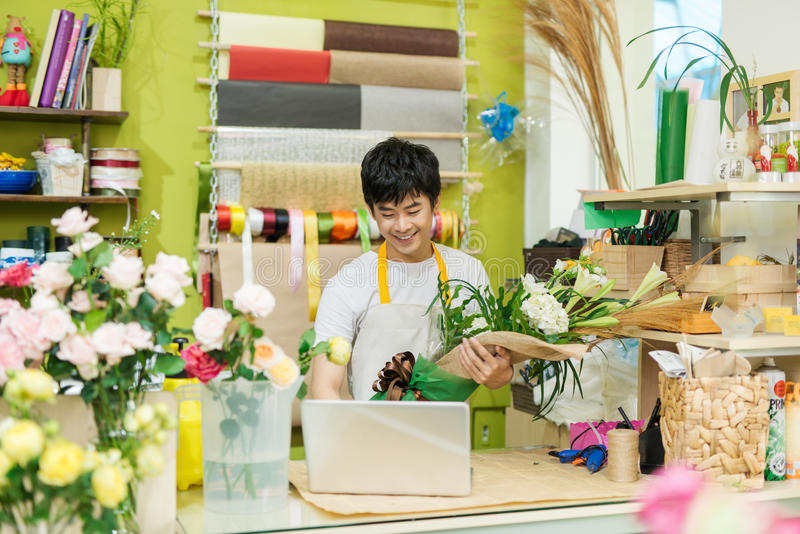 Happy asian male florist using laptop at counter in flower shop royalty free stock image