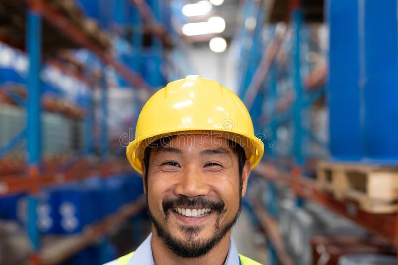 Happy Asian male worker looking at camera in warehouse. Close-up of happy Asian male worker looking at camera in warehouse. This is a freight transportation and stock photo
