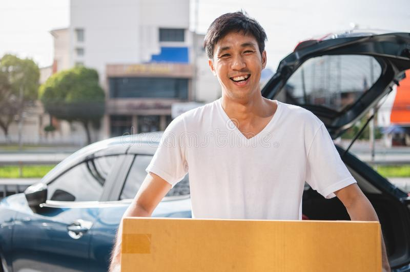 Happy Asian man is delivering cardboard box to customers via private car. People lifestyles and business occupation concept. Young royalty free stock photography