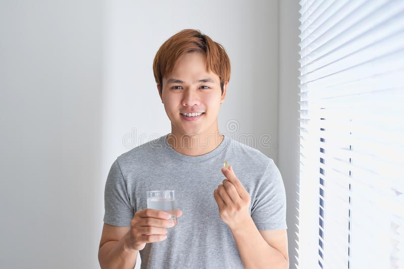 Happy asian man holding omega 3 vitamin pill at home.  royalty free stock photography