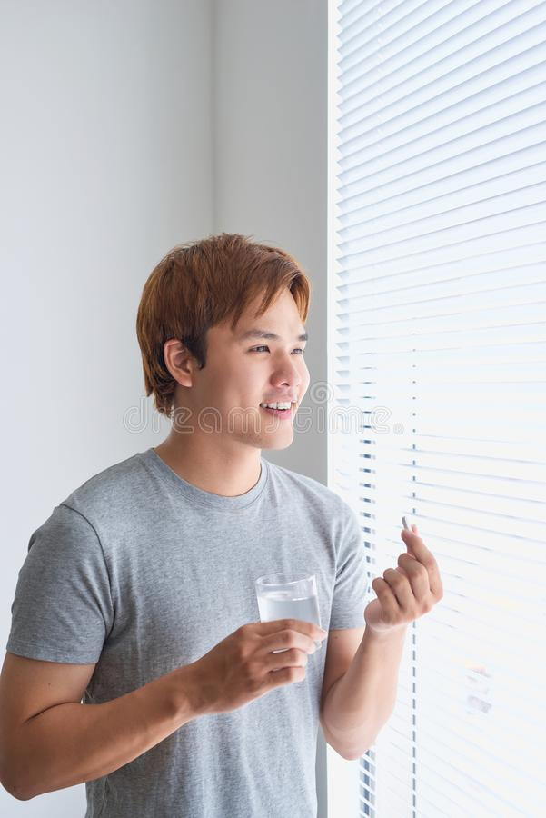Happy asian man holding a pill and a glass of water looking at c. Amera stock image