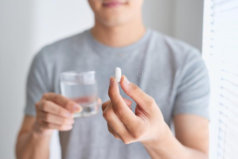 Happy asian man holding a pill and a glass of water looking at c. Amera stock photography
