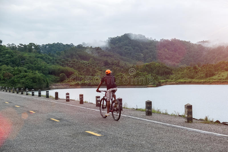 Happy Asian Man Riding Bicycle on Rural Road Look To Nature Ready to Start Vacation Go Adventure Trip, Explore, Discover World royalty free stock photos