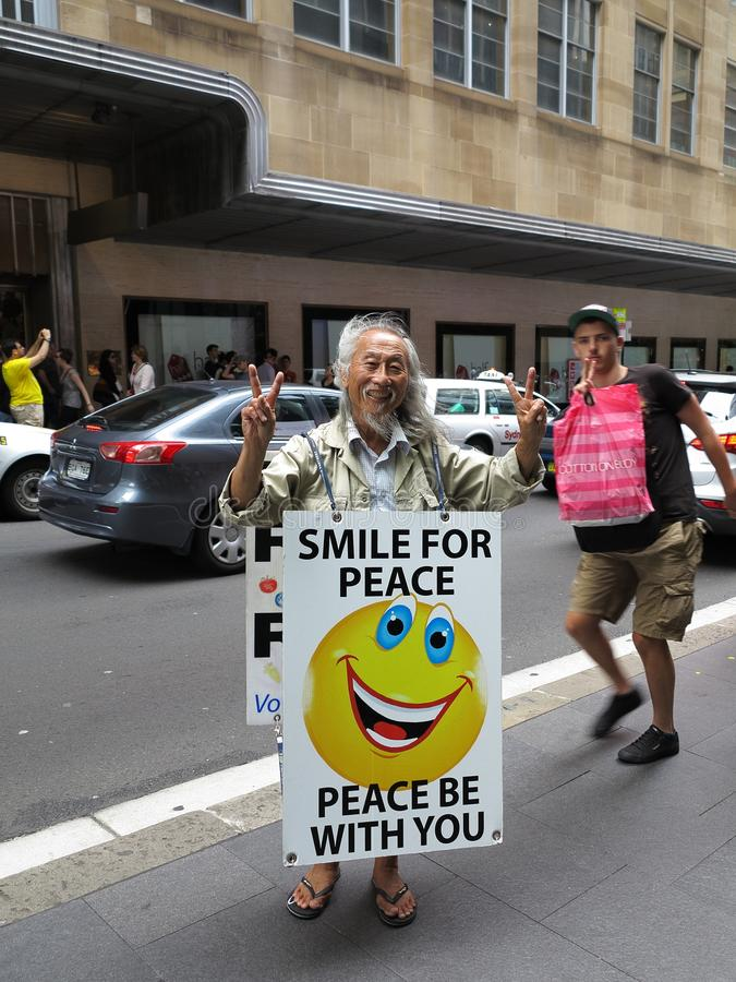 Happy Asian man in sandwich-board and guy photobombing. Happy Asian man wearing a sandwich-board declaring PEACE BE WITH YOU - and a guy who liked to photobomb royalty free stock image