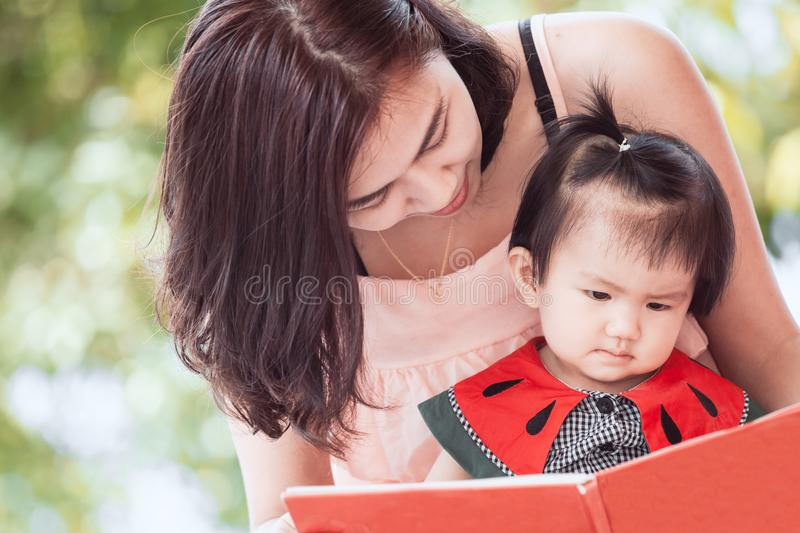 Happy asian mother and cute little baby girl reading a book stock photo