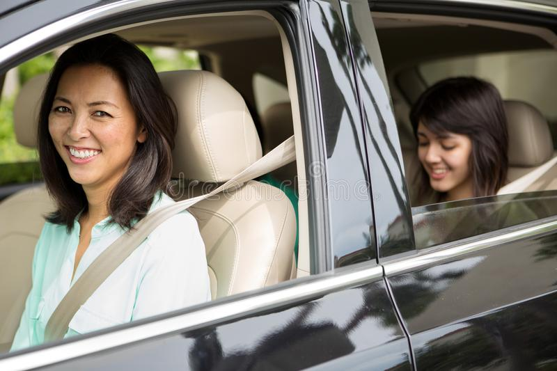 Happy Asian mother driving her teen daughter. royalty free stock photography
