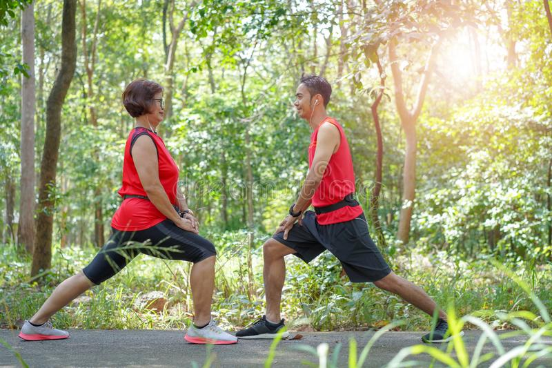 Happy asian mother and son jogging running in the park royalty free stock image