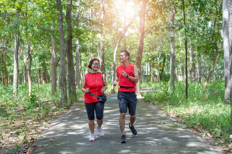 Happy asian mother and son jogging running in the park royalty free stock photography
