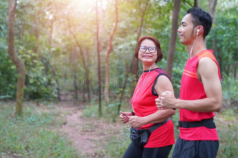 Happy asian mother and son jogging running in the park stock photography