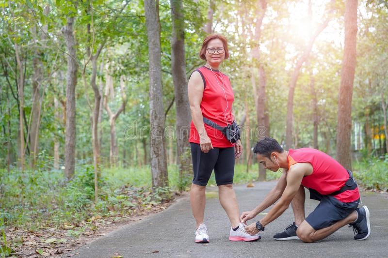 Happy asian mother and son tying shoe laces in the park stock image