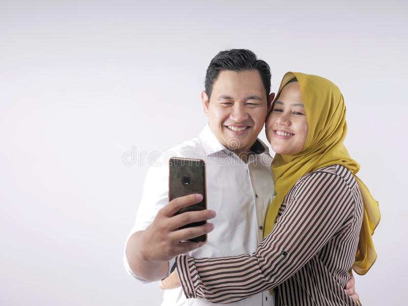 Happy Asian Muslim Couple, Taking Selfie Picture on Smart Phone royalty free stock photography