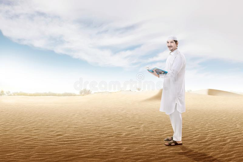 Happy asian muslim man holding the open quran standing on the sand dune. With blue sky background stock photo