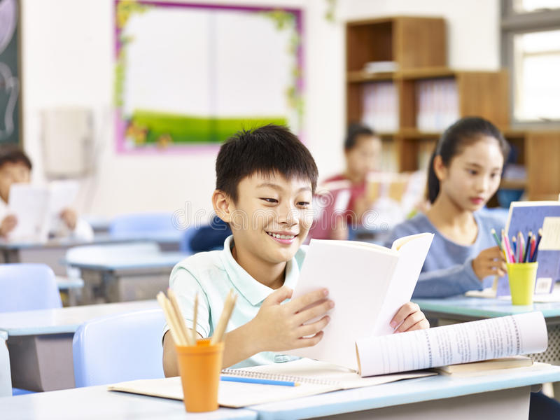 Happy asian pupil in class stock image