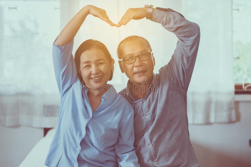 Happy asian senior couple showing hands heart shape together,Happy and smiling,Positive thinking royalty free stock photography