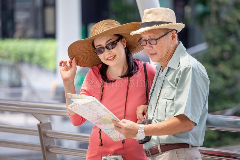 happy asian Senior couple tourists traveling looking at map and searching destination in urban city outdoors.  old man Travellers stock photos
