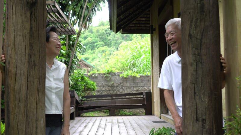 Happy Asian senior elder hide and seek playful stock images