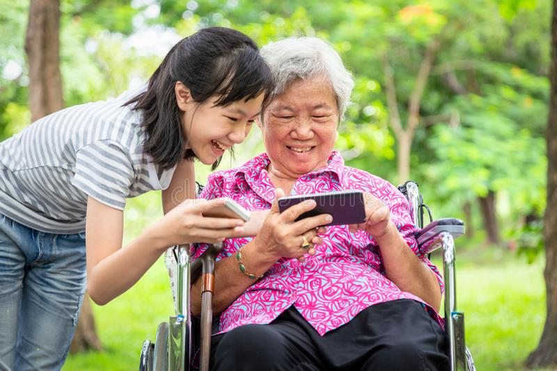 Happy asian senior grandmother and little child girl using cellphone together,playing video game on smart phone,smiling elderly. Woman in wheelchair stock photography
