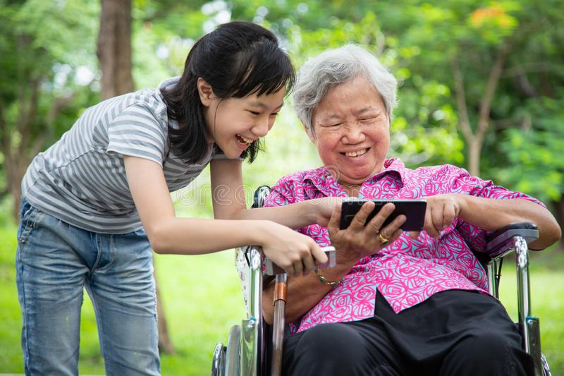 Happy asian senior grandmother and little child girl using cellphone together,playing video game on smart phone,smiling elderly stock photography