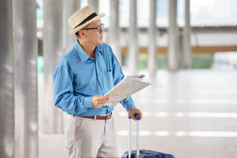 happy asian Senior man tourists   sightseeing with map and searching destination in urban city outdoors.  old Travellers lifestyle stock photography