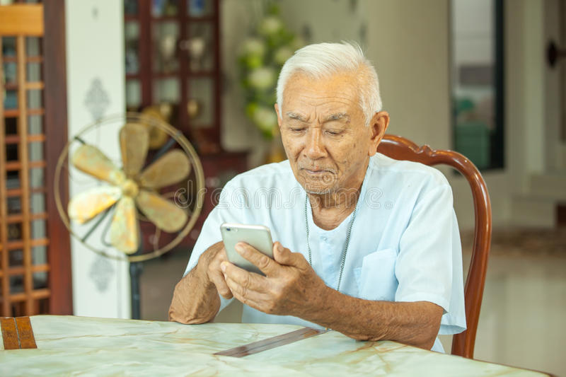 Happy asian senior man using the mobile phone royalty free stock images