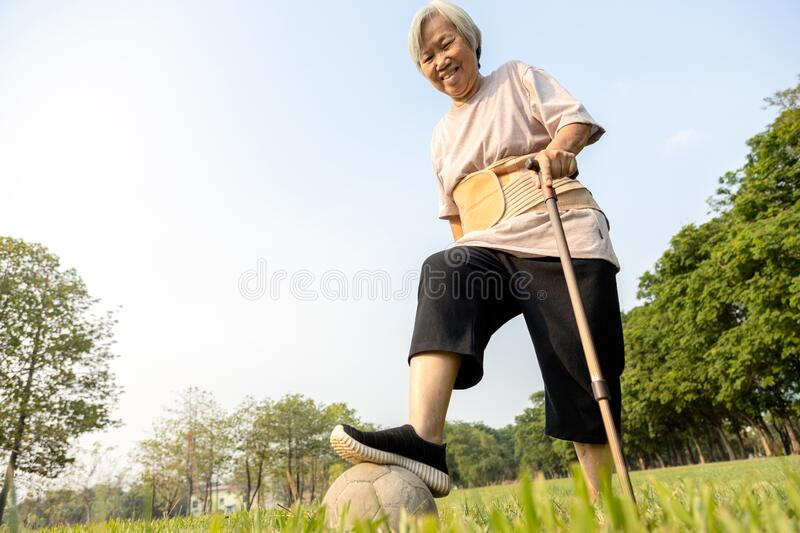 Happy asian senior woman exercising has lost so much weight and excellent healthy with soccer ball,active female elderly playing stock photo