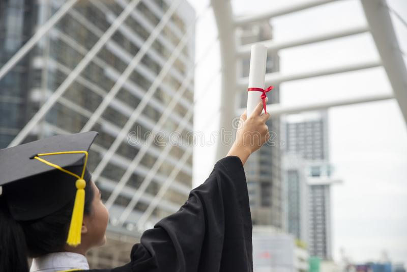 Happy Asian student woman winning graduate diploma. And MBA degree in college,wearing academic dress and cap.Graduate Student and Success Education in stock photos
